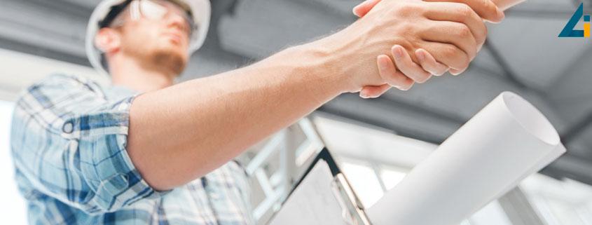 Consultantul in constructii, tine planurile unui imobil si se intelege cu clientul, dand mana pentru a marca incheierea unui contract