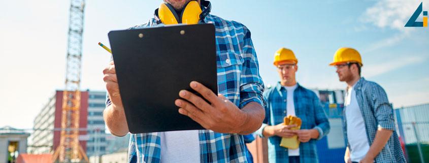 Ingineri constructori pe santier, noteaza in clipboard si discuta cu privire la dirigentia de santier